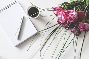 Pink_rose_bouquet_with_a_coffee_mug_and_a_notepad